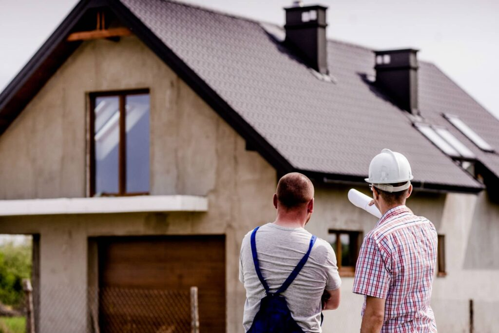 Builder and architect in front of a house and making plannings for a loft conversion