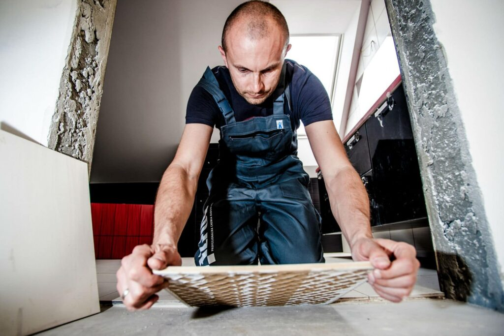 A builder laying flooring during a loft conversion
